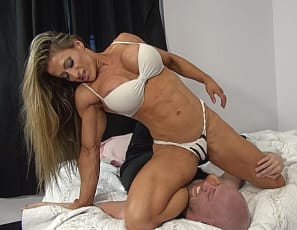 Female muscle beauty Maria G is having her way with Dante again. Using her powerful biceps and legs to humble Dante and using her perfect pecs and glorious glutes to smother him. Still, you have to admit - you'd love to be wrestling this profession female bodybuilder wouldn't you? Of course you would!