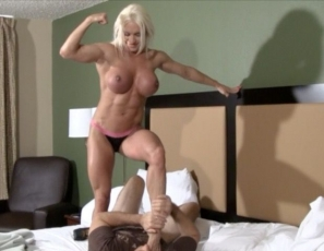 Nude female bodybuilder Ashlee Chambers continues wrestling with her fan. This time she adds a handjob, some light cock and ball torture and takes off her panties to show us all her amazing big clit! He's getting his ass kicked, but this is one lucky fan :)