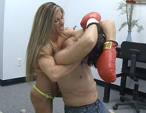 Maria G's opponent has his boxing gloves on and is ready to fight, but he can't compete with her ripped female muscle as she wrestles him, smothering him with her powerful pecs, legs, glutes and calves and her strong, vascular biceps and abs. She wins the fight – in high-heeled shoes!